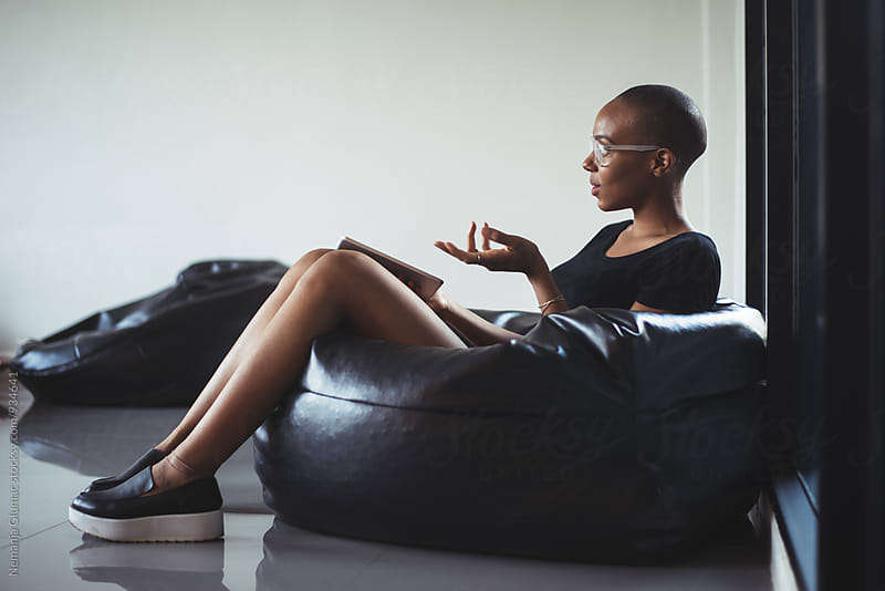African American Woman in a Bean Bag Talking to Someone by Nemanja Glumac for Stocksy United