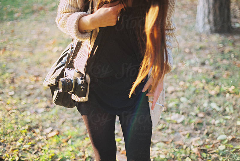 Fashionable girl with analogue camera in a park during an autumn day by VeaVea for Stocksy United
