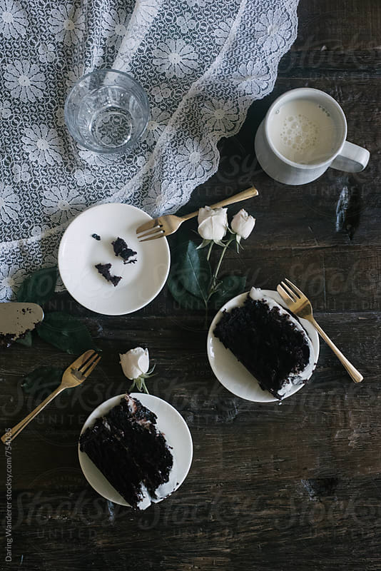Slices of chocolate cake, white mini roses and glass of milk styled on lace and dark wood table by Daring Wanderer for Stocksy United