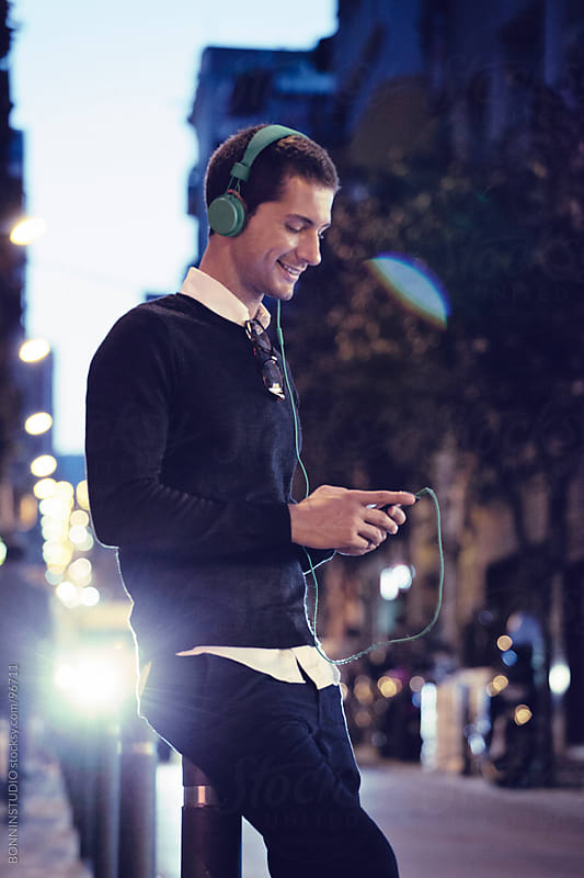 Modern casual man on the street smiling. He is listening music on phone with headphones. by BONNINSTUDIO for Stocksy United