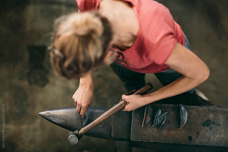 Young woman using hammer and anvil  by Lior + Lone for Stocksy United