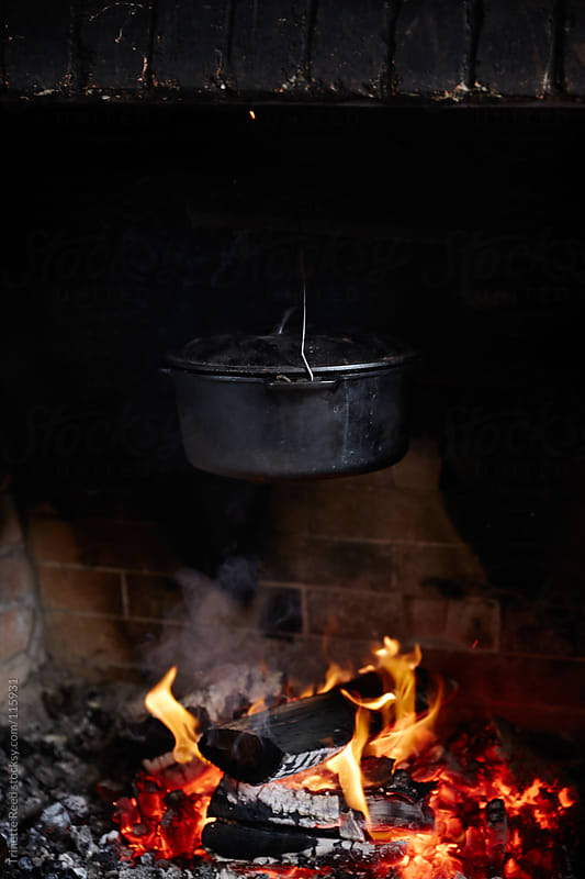 Cast iron pot cooking over an fire heart inside a cabin by Trinette Reed for Stocksy United