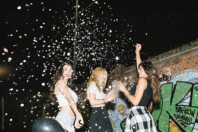 Women dancing under a confetti rain by Simone Becchetti for Stocksy United