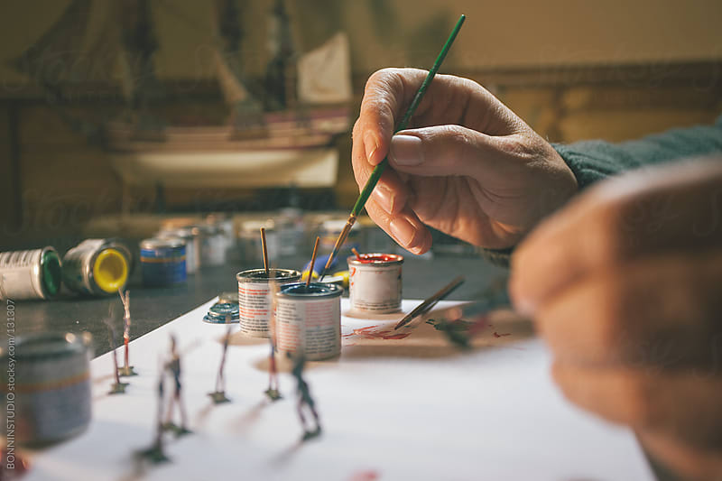 Restorer working and painting old tin soldiers. by BONNINSTUDIO for Stocksy United