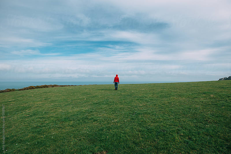 Man walking in a field by Aila Images for Stocksy United