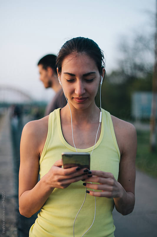 Woman in sportswear browsing on her mobile phone by Marija Mandic for Stocksy United