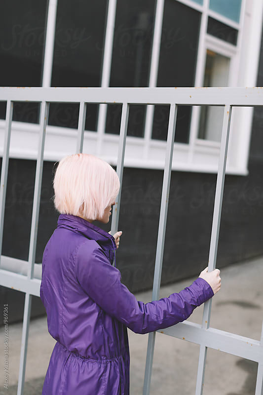 Young woman looking through a fence . by Alexey Kuzma for Stocksy United