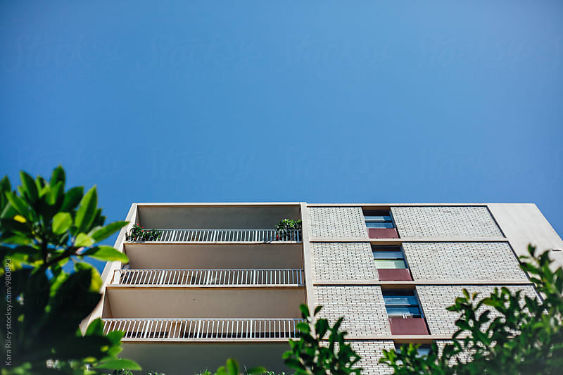 Apartment Building - Bright Blue Sky by Kara Riley for Stocksy United
