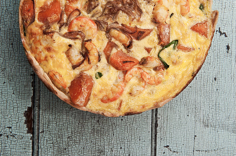 shrimp quiche on rustic tabletop, top down view by Gillian Vann for Stocksy United