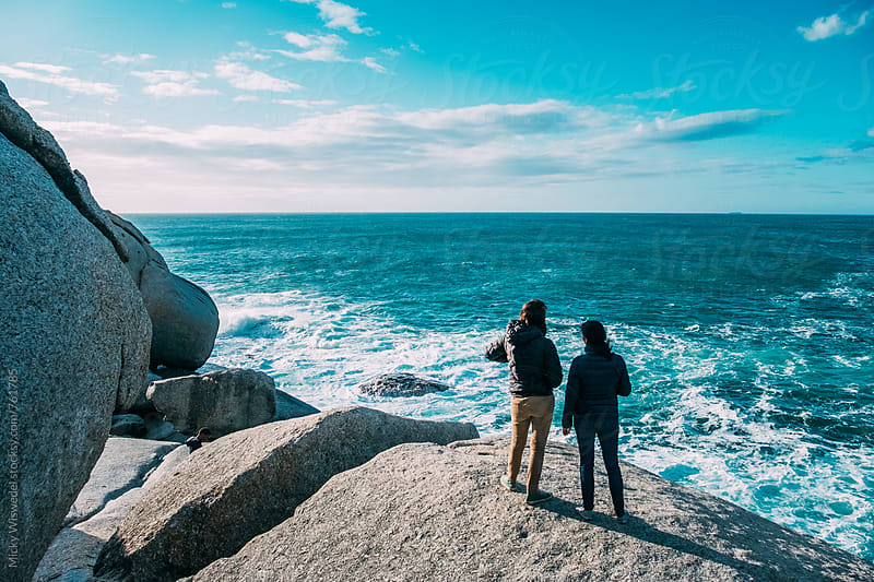 Friends watching the sea from a rocky platform by Micky Wiswedel for Stocksy United