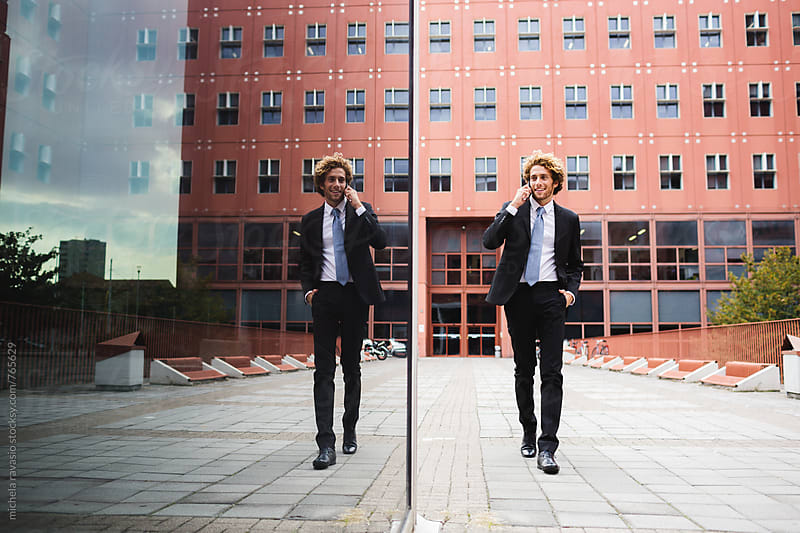 Smiling businessman walking reflected in a glass building by michela ravasio for Stocksy United