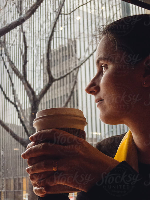 Woman with Coffee Looking Out at Rainy City by Geoffrey Hammond for Stocksy United