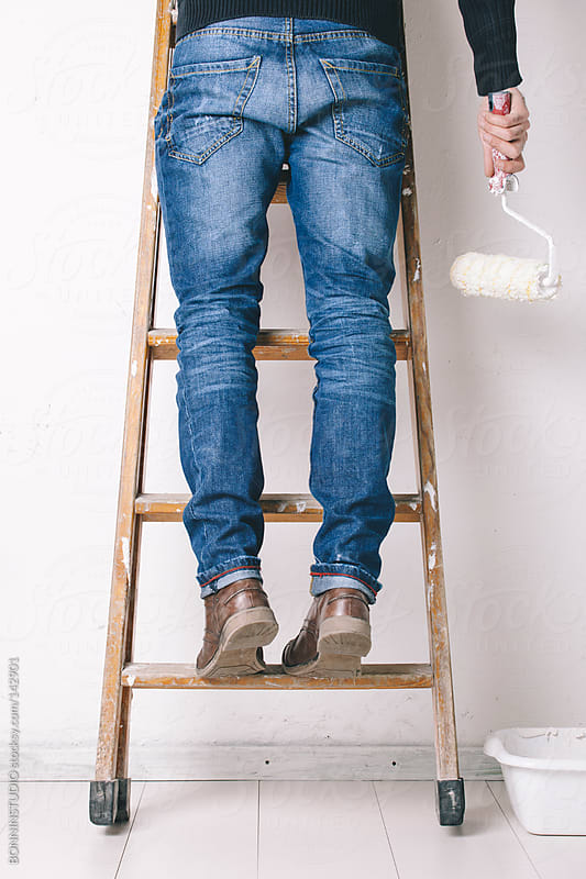 Man painting a wall on a wood ladder. by BONNINSTUDIO for Stocksy United