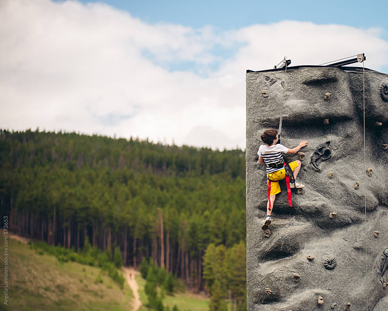 Boy climbing a rock wall by Angela Lumsden for Stocksy United