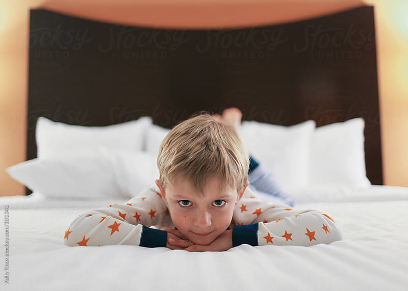 young boy lying on a hotel bed by Kelly Knox for Stocksy United
