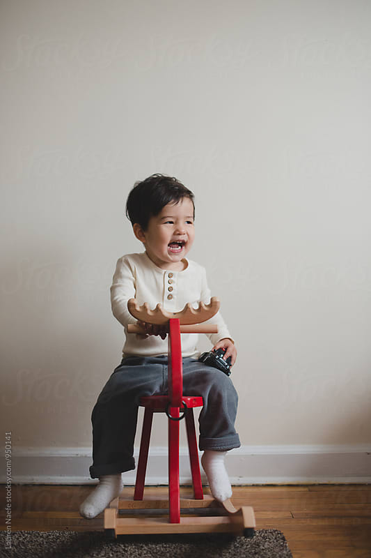 Toddler on rocking horse by Lauren Naefe for Stocksy United