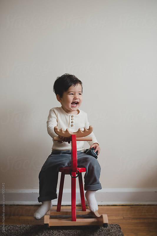 Toddler on rocking horse by Lauren Naefe for Stocksy United