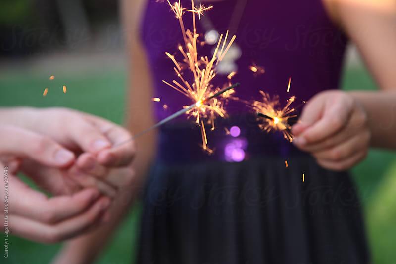Friends  lighting sparklers on a holiday by Carolyn Lagattuta for Stocksy United