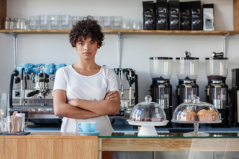 Portrait of beautiful young cofee shop owner behind the counter by W2 Photography for Stocksy United