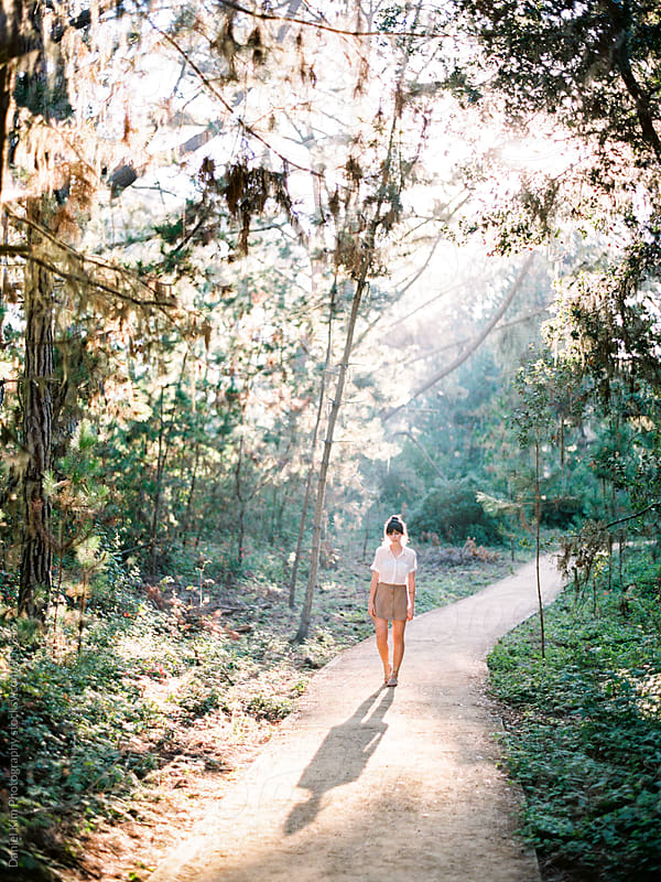 Woman walking on forest trail by Daniel Kim Photography for Stocksy United
