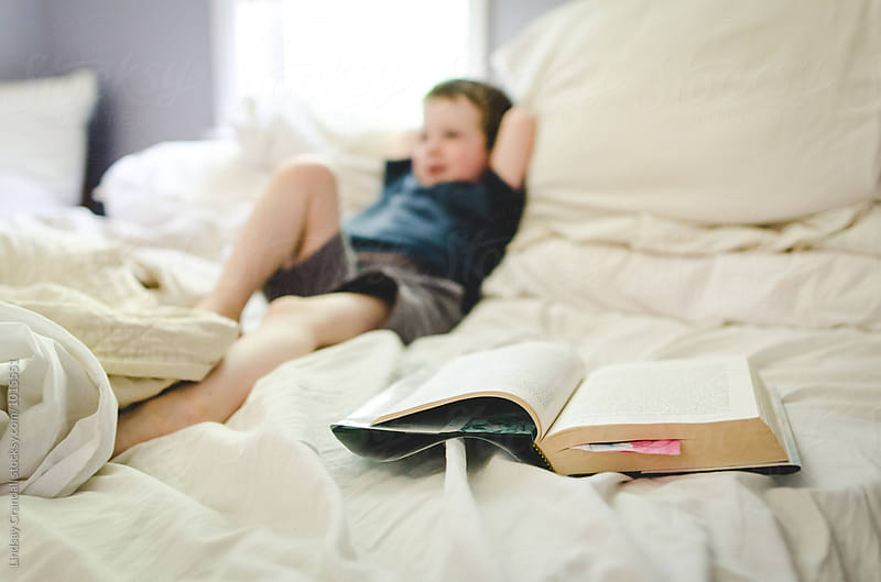 Child lying in bed beside open chapter book by Lindsay Crandall for Stocksy United