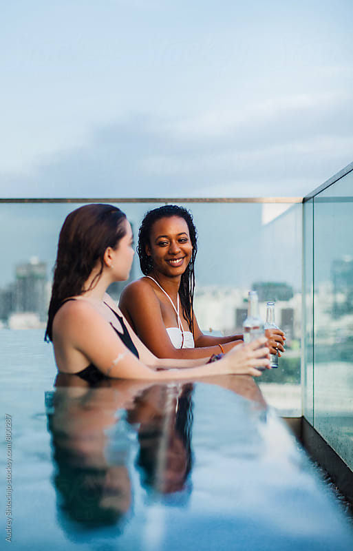 Two girlfriends having fun chat in swimming pool with city skyline behind them. by Audrey Shtecinjo for Stocksy United