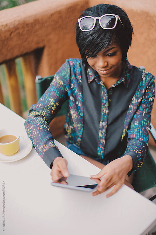 Black girl reading a tablet smiling by Gabrielle Lutze for Stocksy United