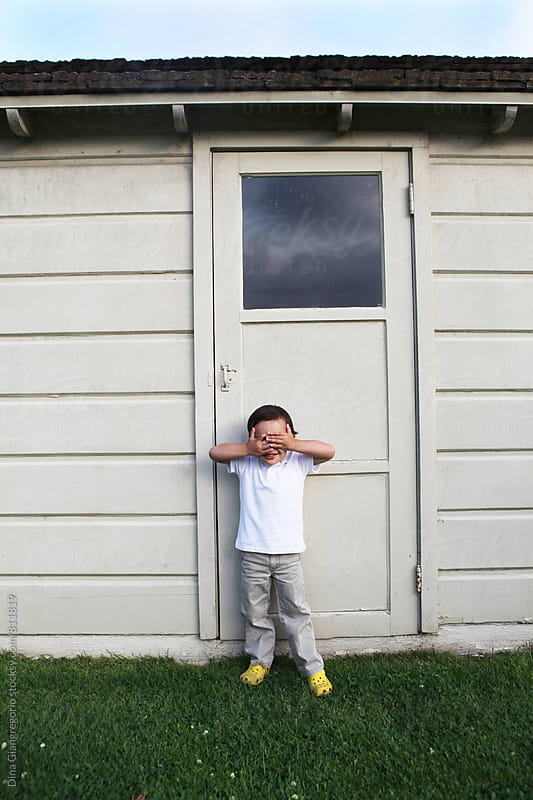 Boy Standing in Front of House Covering His Eyes by Dina Giangregorio for Stocksy United