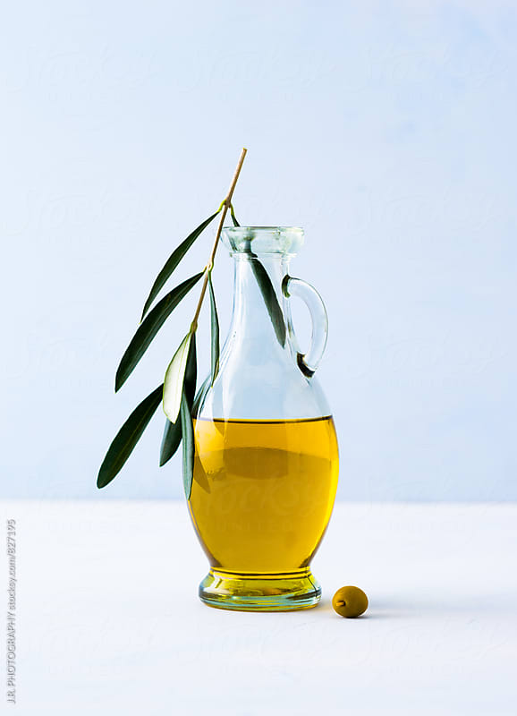 Carafe of olive oil and and twig of an olive tree by J.R. PHOTOGRAPHY for Stocksy United