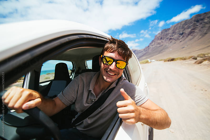 Man in a car on scenic road in sunglasses with thumb up out of the window by Alejandro Moreno de Carlos for Stocksy United