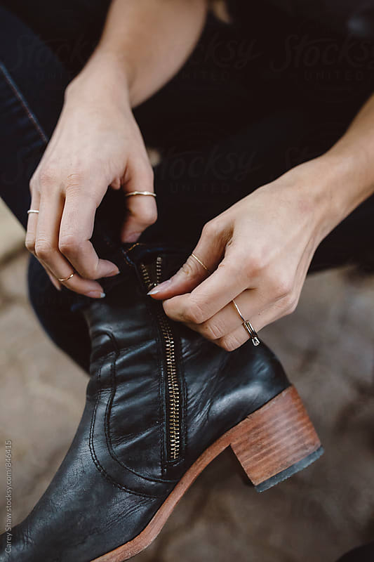 Woman putting on stylish boots by Carey Shaw for Stocksy United