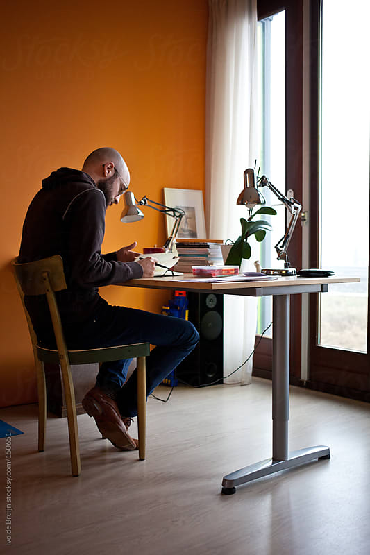Designer working at his desk at his home office by Ivo de Bruijn for Stocksy United