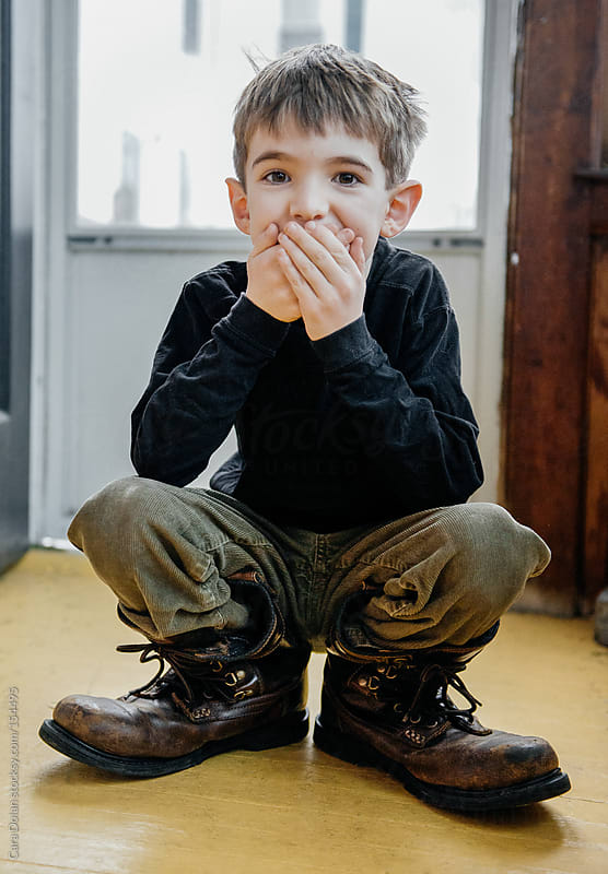 Cute boy giggles while wearing his father's too-big boots by Cara Dolan for Stocksy United