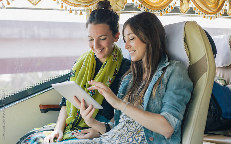 Girlfriends traveling together and watching a movie on tablet by Jovo Jovanovic for Stocksy United