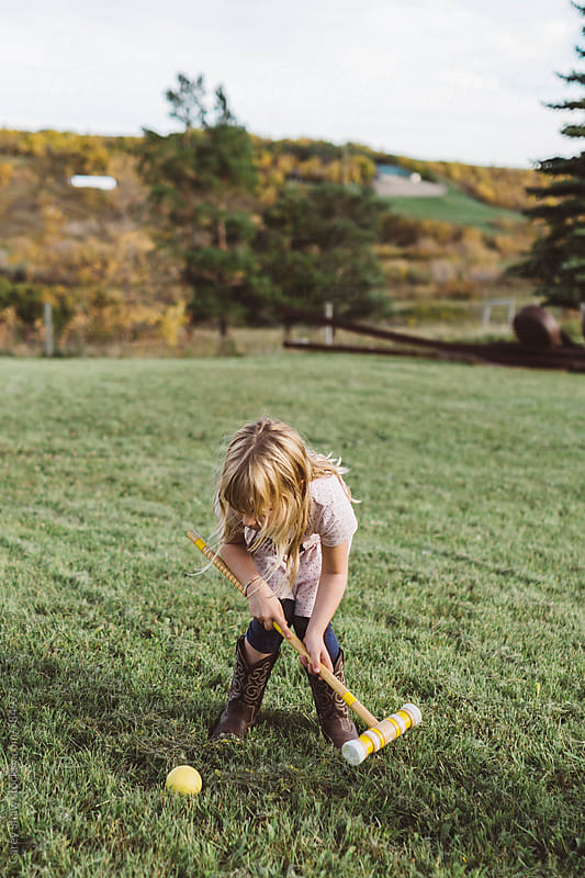Young girl hitting ball with croquet mallet by Carey Shaw for Stocksy United