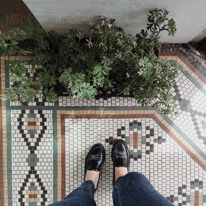 looking down at two shoes standing on a tiled floor with plants by KATIE + JOE for Stocksy United