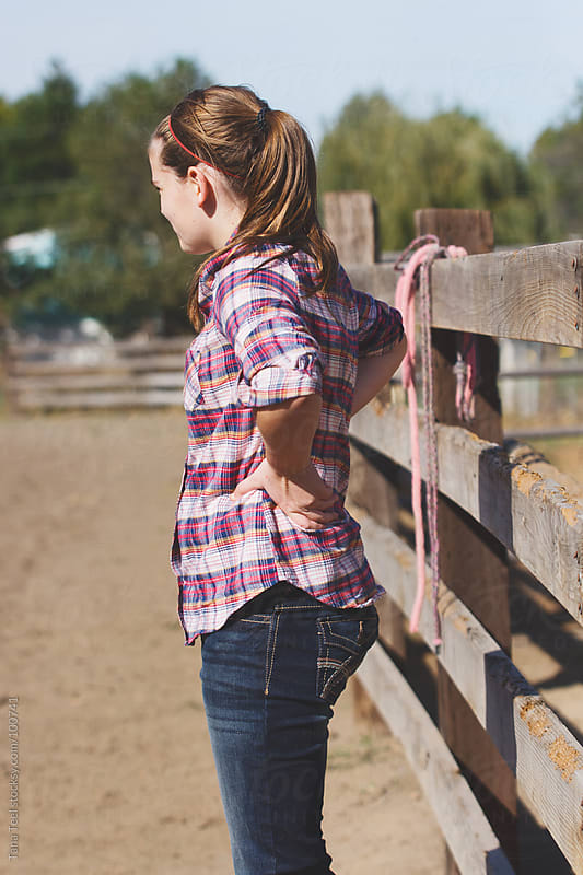 Country girl stands along the fence inside an arena by Tana Teel for Stocksy United