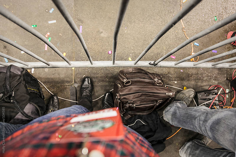 Journalists' feet standing at an event barrier.  by Holly Clark for Stocksy United
