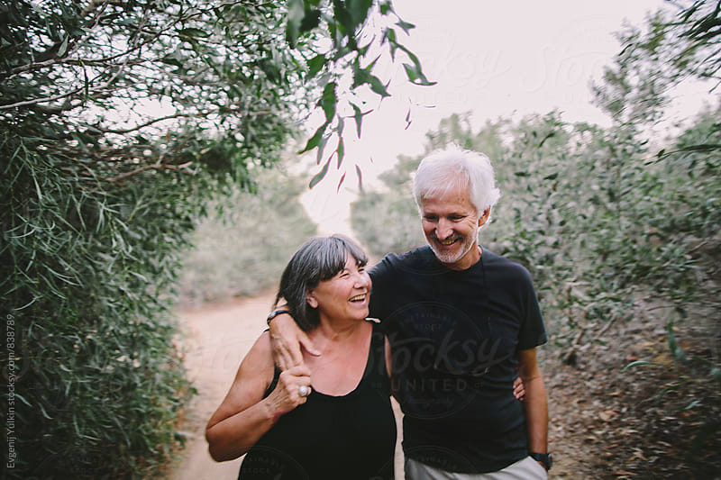 Old couple waking on the path and laughing by Evgenij Yulkin for Stocksy United