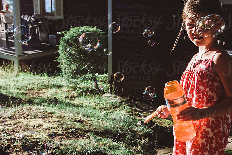 A little girl blows bubbles on a summer day. by Holly Clark for Stocksy United