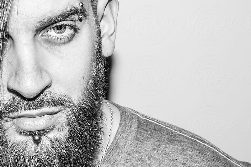 black and white portrait of a beautiful young man with a beard and piercing by Igor Madjinca for Stocksy United