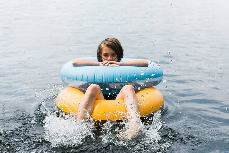 Boy floats on a lake with two innertubes by Cara Slifka for Stocksy United