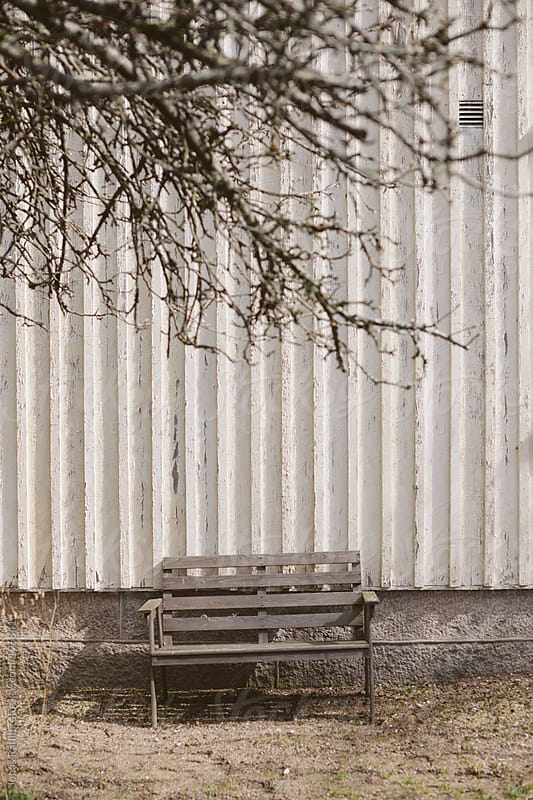 Empty bench in front of a white wall by Jonas Räfling for Stocksy United