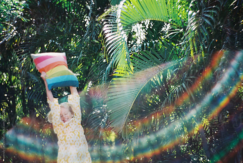 girl in yellow dress with rainbow pillow against green palms with rainbow flare by wendy laurel for Stocksy United