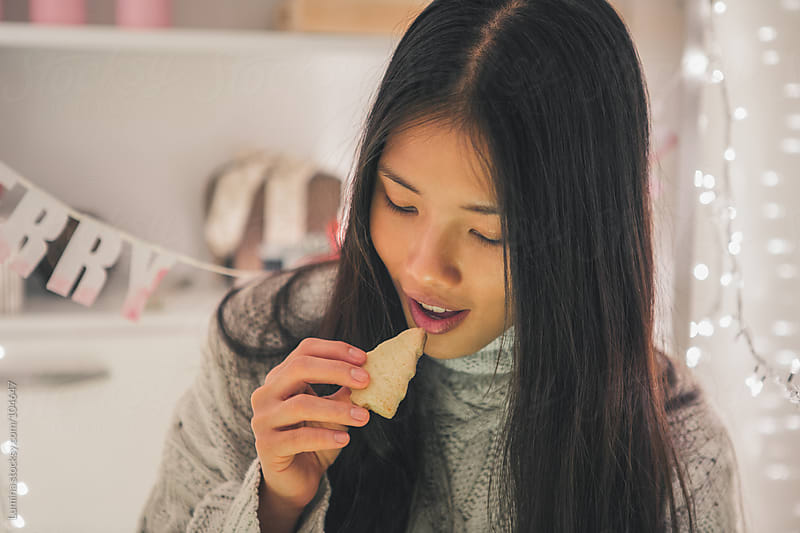Woman Eating a Christmas Cookie by Lumina for Stocksy United