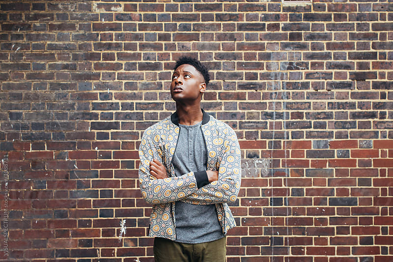 London Street Style - Outdoor Portrait of Good-Looking Young Black Man Standing in Front of Exposed Brick Wall and Looking Up by Julien L. Balmer for Stocksy United