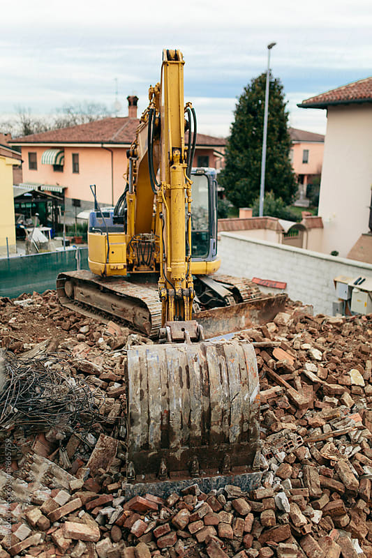 Above sight of bulldozer parked on top of ancient building ruins in Italy by Laura Stolfi for Stocksy United