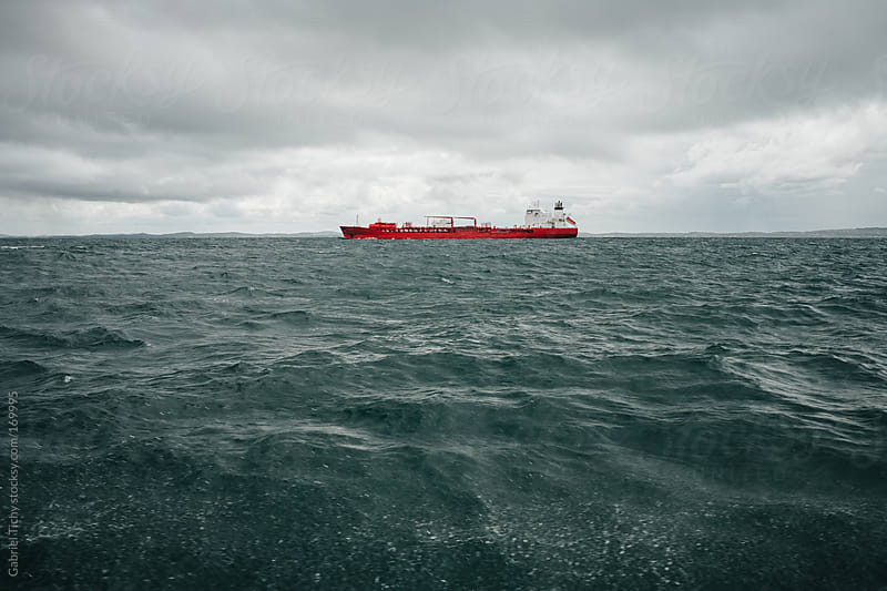 Red tanker in stormy sea by Gabriel Tichy for Stocksy United