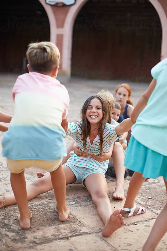 Group of boys and girls playing in a happy mood by Miquel Llonch for Stocksy United