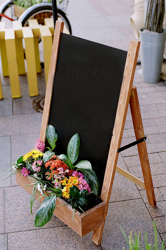 Chalkboard sign with flowers at the entrance  by Lyuba Burakova for Stocksy United